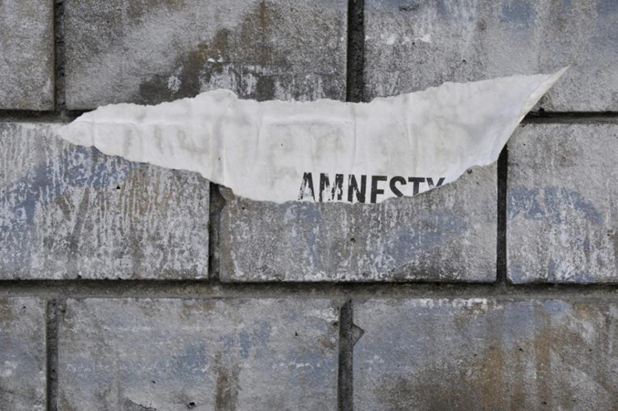 Auf einer Mauer ein abgerissenes Papier mit der Aufschrift Amnesty, Foto von Ieva Jansone