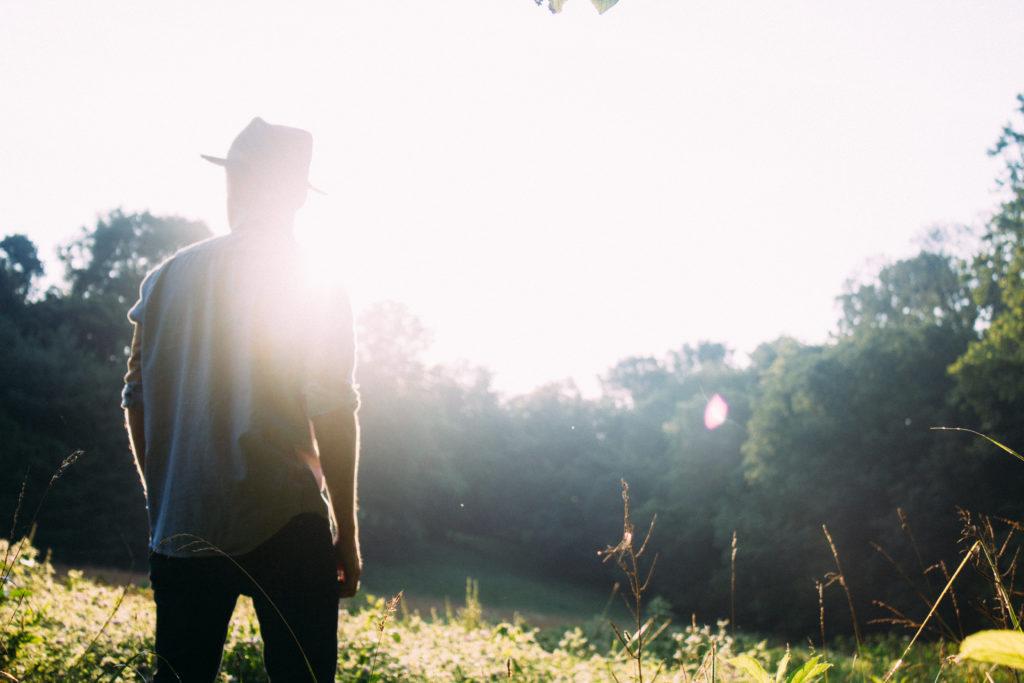 Das Bild zeigt einen Mann von hinten im Gegenlicht. Er traegt einen Hut