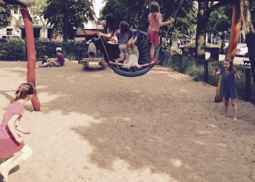 Kinder beim Schaukeln auf dem Spielplatz