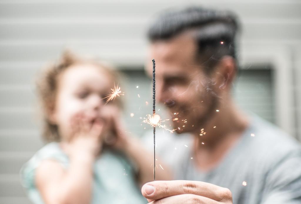 Das Bild zeigt einen Vater mit Tochter. Er haelt eine Wunderkerze