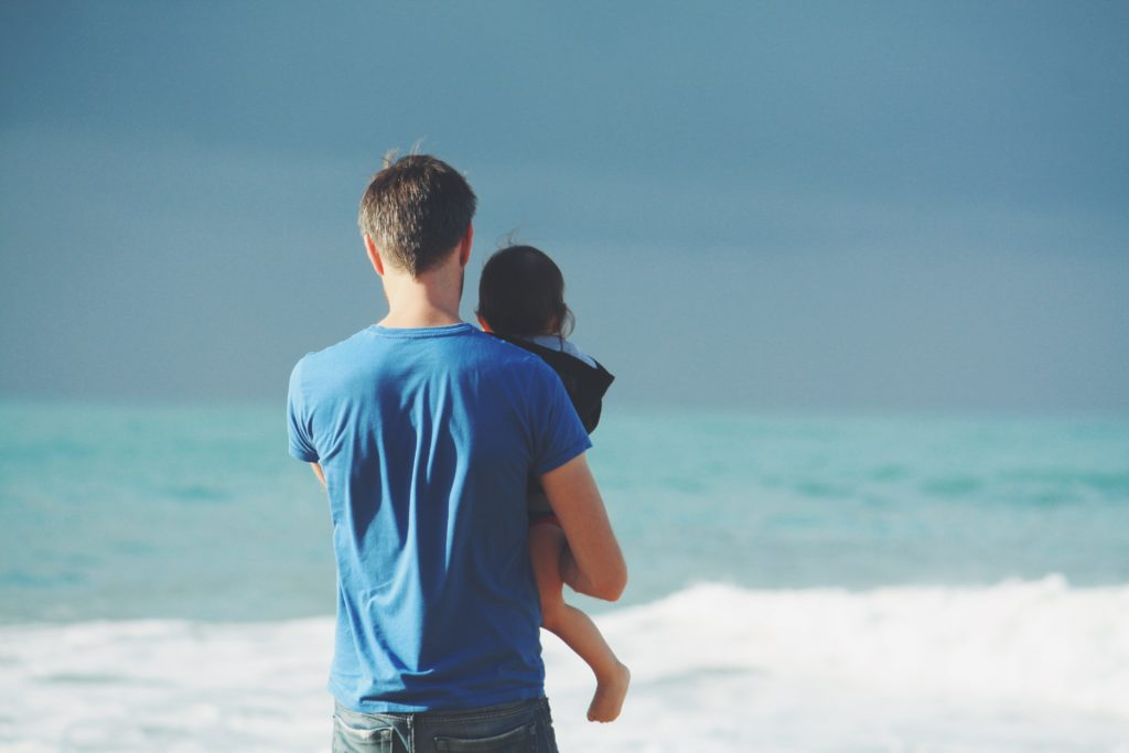 Das Bild zeigt einen Mann von hinten. Er hat ein Kind auf dem Arm und steht mit dem Ruecken zum Meer